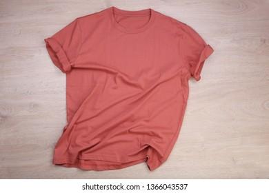 Wrinkled orange pastel t-shirt on wooden background