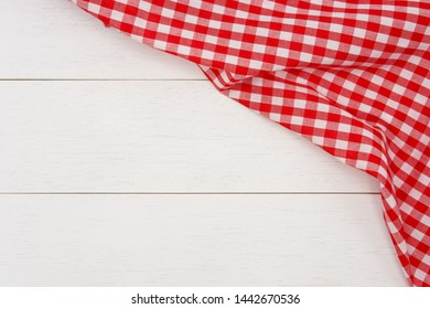 Wrinkled red gingham fabric on rustic white wood plank background, with copy space.