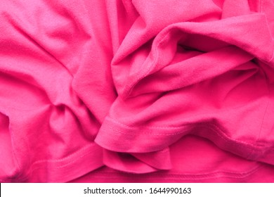 Wrinkled shirt soft pink fabric texture. Crumpled cloth background, light wavy clothing material, old worn apparel close up top view