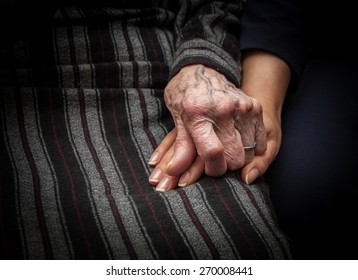 Wrinkled skin hand of aged woman holding hand of young lady