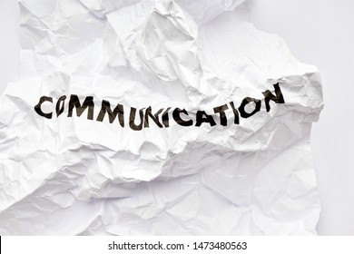 Wrinkled white paper with the word communication printed in black. Concept of bad disrupted communication or miscommunication.