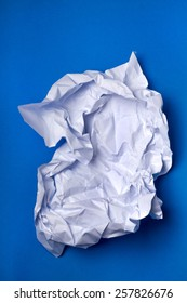 Wrinkled white piece of paper over a blue background.