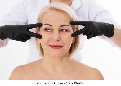 Falten beim Altern und Botox-Injektionskonzept - schöne Frau mittleren Alters und Hände eines plastischen Chirurgen einzeln auf weißem Hintergrund, Nahaufnahme