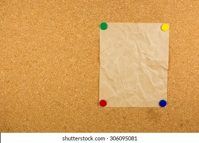 wrinkles paper on cork board with 4 sticky note pinned