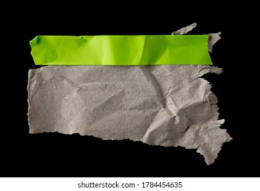Wrinkly brown paper scrap with green sticky tape isolated on black background and texture, top view