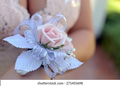 Wrist corsage with pink roses and silver ribbon and leaves, worn on wrist of beautiful girl