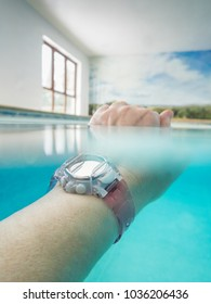 wrist and hand wearing a pink plastic water resistant watch in a swimmng pool. The watch is under water the hand above water