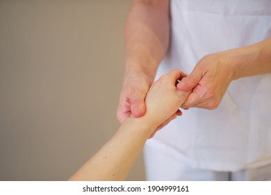 Wrist massage. massage therapist puts pressure on a sensitive point on a woman's hand. Physiotherapist massaging her patients hand in medical office