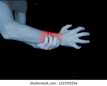 Wrist pain market with read spot on black background.