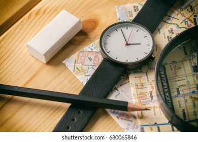 Wrist watch, magnifiers, pencils, erasers, and city maps are placed on wooden boards. Like being a detective or a tourist. Shallow depth of field. Focus to Whist watch. Vintage Style. Instagram.