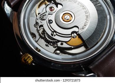 Wrist watch with metal gears and cogwheels. Clock mechanism macro shot.
