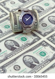 Wrist watch with a money roll on a background of two dollar bills.
