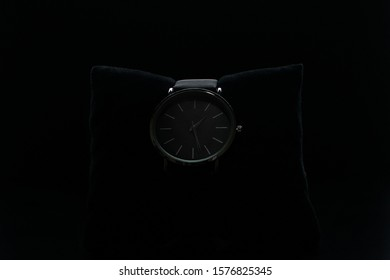 Wrist watch on a black background. Watch in a case on a black velvet pillow
