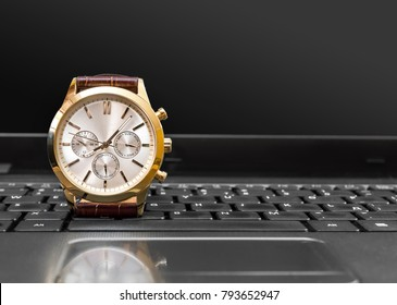 Wrist watch on the laptop keyboard.