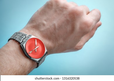 Wrist watch on man's hand. Plate, knife and fork on clock face. Concept of intermittent fasting, lunchtime