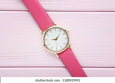 Wrist watch on pink wooden table