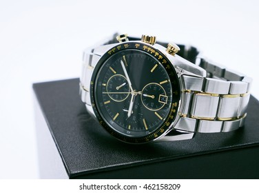 Wrist watch with stainless steel on black box on white background. Copy space. Selective focus.