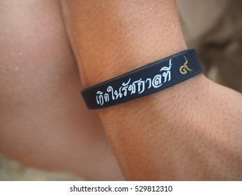 """wristband saying """"I was born in the reign of KING RAMA IX"""""""