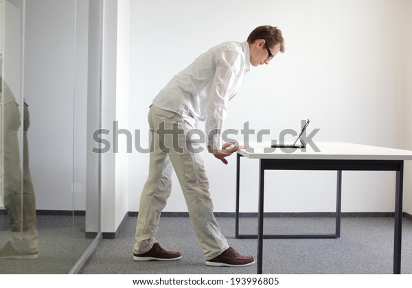 wrists exercise during office work - standing man reading at tablet in his office