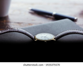 Wristwatch with extendable in brown color on leather notebook with patterns and blue pen