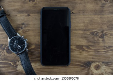 Wristwatch and mobile phone on wooden table. Natural photo.