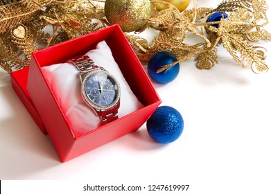 Wristwatches in a red gift box, Christmas decorations on a white background
