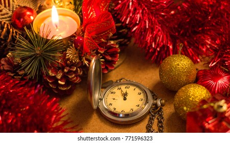 Wristwatches show without five twelve minutes with a candle, a tinsel.