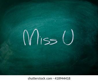 "write a chalk ""Miss U"" on a black board"