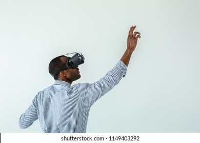 Write it down. Waist up of pleasant afro american man using a board while testing VR glasses