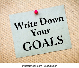 Write Down Your Goals Message written on recycled paper note pinned on cork board. Motivational concept Image