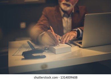 Write down your obligations. Senior business man working at home. Focus on hand.