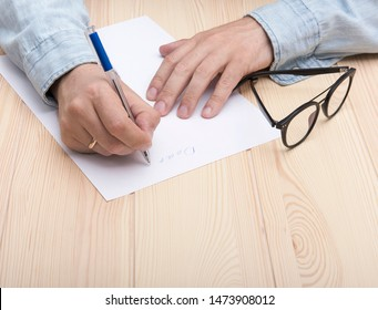 write a letter. In the hands of a man is a ballpoint pen and he writes a letter. Wedding ring on the hand. On a white sheet is the beginning of the letter. Nearby are glasses.