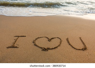 write I love you on the sand with the wave for background