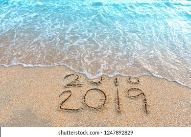 Write a number message Year 2018 replace 2019 written on beach sand background. Good bye 2018 hello to 2019 happy New Year coming concept.