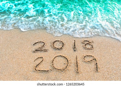 Write a number message Year 2018 replace 2019 written on beach sand background. Good bye 2018 hello to 2019 happy New Year coming concept