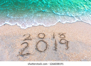 Write a number message Year 2018 replace 2019 written on sea beach sand background. Good bye 2018 hello to 2019 happy New Year coming concept