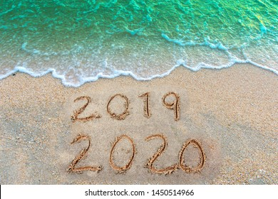 Write a number message Year 2019 replace 2020 written on beach sand background. Good bye 2019 hello to 2020 happy New Year coming concept