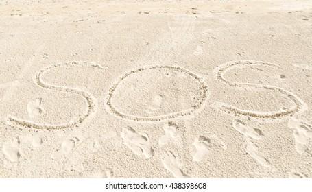 Write SOS on sand at beach near sea,help,daylight