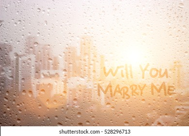 write will you marry me on raining window in first light morning time