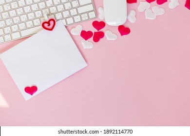 Write wish on white piece of paper for Valentines day on February 14. Celebrate Valentines day on pink background. Office flat lay with red toy hearts and white keyboard and mouse, love concept