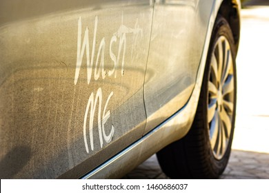 "Write the words ""wash me"" on the very dirty surface of the car. Concept car wash."