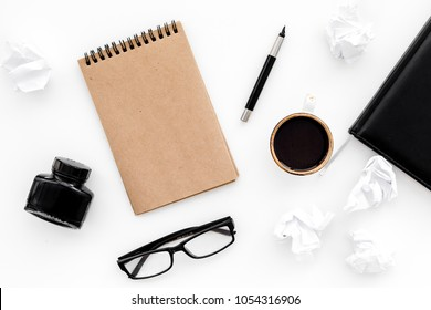 writer office desk with notebook, ink, pen and glasses white background top view space for text