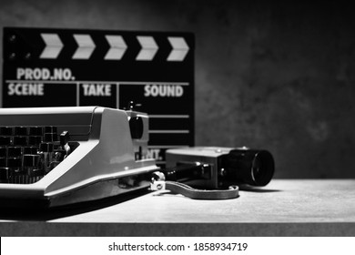 writer or screenwriter concept from vintage retro typewriter, film camera and movie clapper board at table