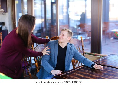Writer with smartwatch on hand waiting business partner in cafe and suddenly meet former classmate, imposing guy wearing blue jacket and black T-shirt checking time looking out window. Asian