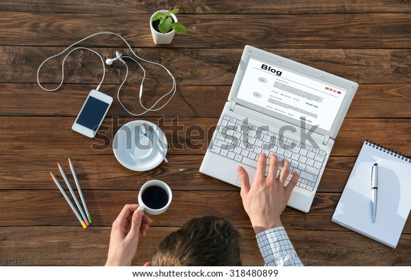 Writer Working on Computer at Wooden Desk Top View of Man Typing on Laptop and Holding Coffee Mug at Warm Natural Wood Table with Electronic Gadgets and Stationery Tools for Every Day Life