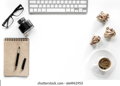 Writer workplace with keyboard, vintage notebook, glasses and coffee on white background top view copyspace