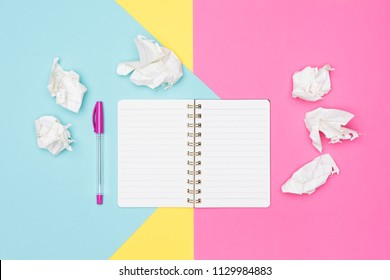 Writer's block. Ideas, brainstorming, creativity, imagination, deadline, frustration concept. Top view photo of office desk with blank mock up open notepad and crumpled paper on pastel background.