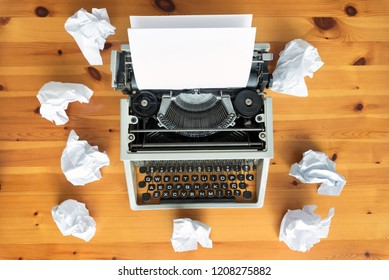 Writer's block. Typewriter and crumpled paper on work desk. Creative process concept