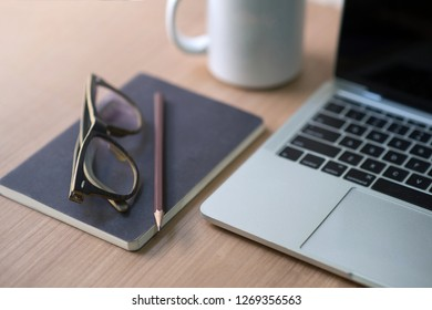 Writer's career on the desk with white coffee mugs, notebooks, pencils, glasses and Macbooks