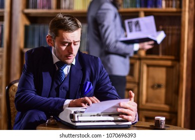 Writers craft and routine concept. Writer or young author with typewriter working on new book in library with friend. Men in suits in library with antique books with bookshelves on background.